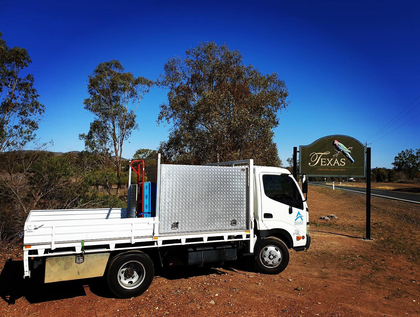 Ausco Industries truck in front of a road sign parked on the dirt - Contact Us